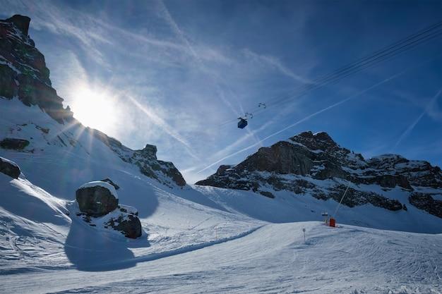 Vista de uma pista de estação de esqui com pessoas esquiando nas dolomitas.