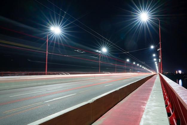 Vista de uma ponte longa e brilhante com luzes frias e carros velozes sobre o grande e belo rio dnieper em dnepropetrovsk na ucrânia