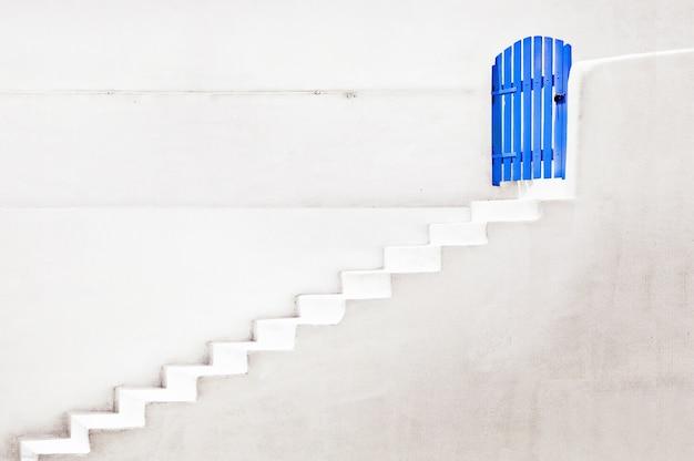 Vista de uma porta de madeira azul com parede branca e escada conceito de portas e escadas