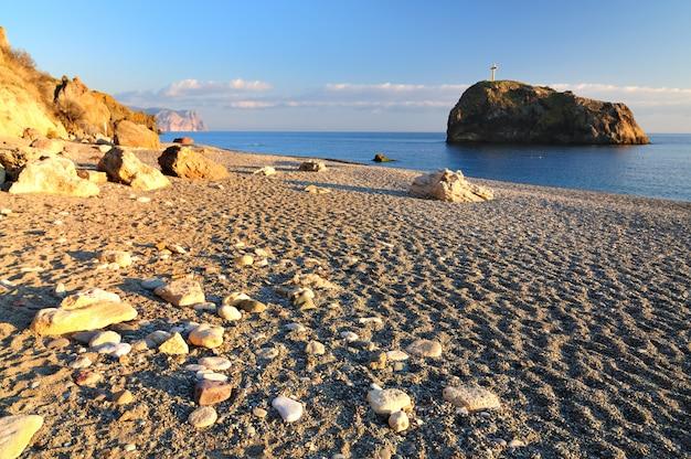 Vista de uma praia com mar calmo e céu claro em um dia ensolarado de verão