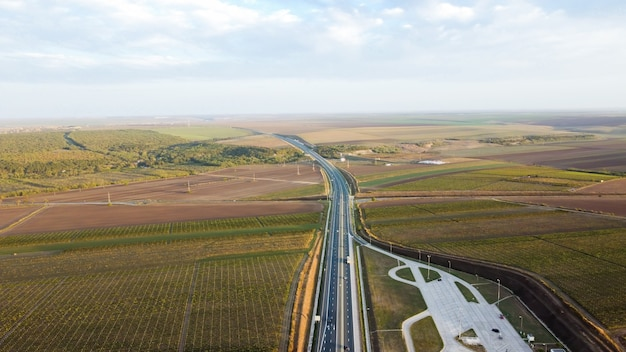 Vista de uma rodovia com carros do drone, estacionamento, campos florestais na romênia