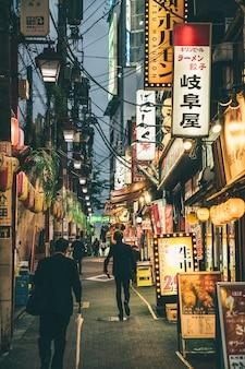 Vista de uma rua na cidade e à noite com luzes e pessoas