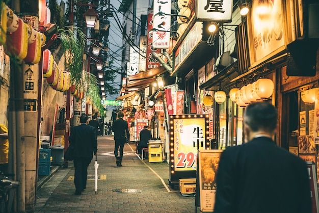 Vista de uma rua na cidade e à noite com pessoas e luzes