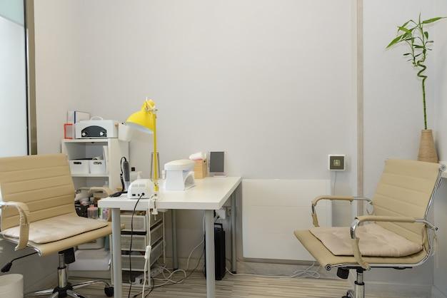 Vista de uma sala vazia de uma clínica médica com equipamentos para manicure