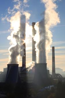 Vista de uma usina termelétrica. a luz do sol rompe o vapor.