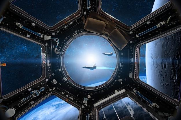 Vista de uma vigia da estação espacial no fundo da terra
