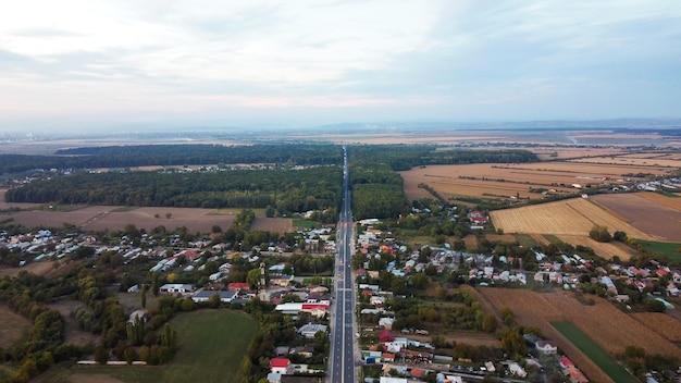 Vista de uma vila e rodovia na romênia, edifícios residenciais baixos, floresta, campos, vista do drone, romênia