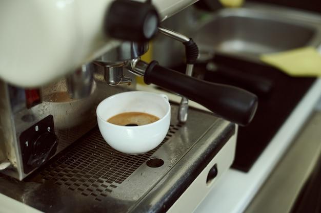 Vista de uma xícara de café expresso em uma cafeteira profissional