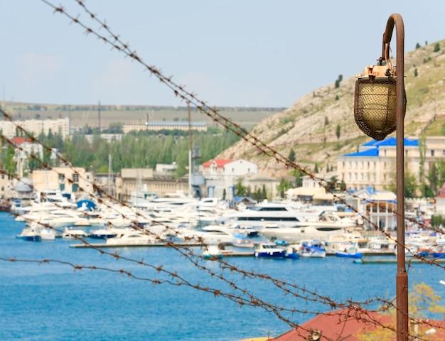 Vista de verão à beira-mar com navios no cais e barblock em primeiro plano (cidade de balaclava, crimeia, ucrânia)