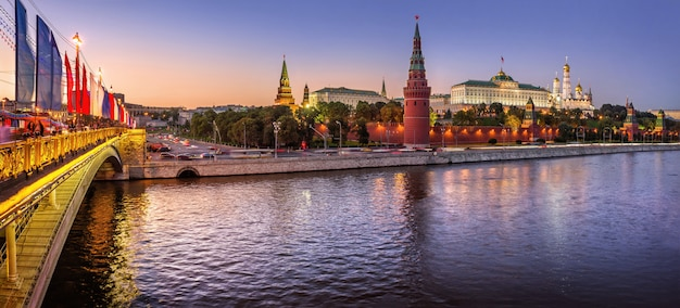 Vista de vodovzvodnaya, outras torres e templos do kremlin de moscou e as bandeiras da ponte de pedra grande