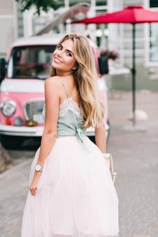 Vista de volta pin up estilo garota com longos cabelos loiros, andando na rua. ela está sorrindo para a câmera.