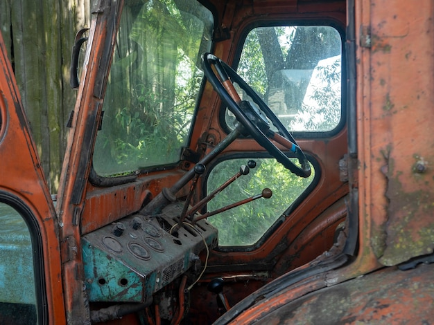 Vista dentro da velha e enferrujada cabine do trator. maquinário agrícola abandonado