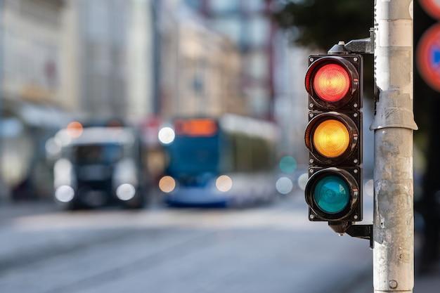 Vista desfocada da cidade com semáforos, em primeiro plano um semáforo com luzes vermelhas e amarelas