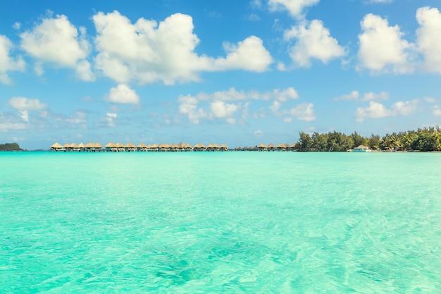 Vista deslumbrante da lagoa azul turquesa e bungalows distantes da ilha de bora bora, polinésia francesa