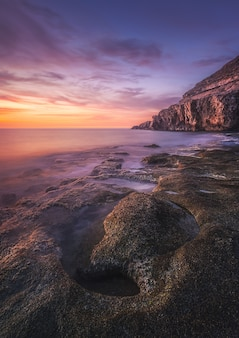 Vista deslumbrante da paisagem marítima e das rochas no dramático pôr do sol