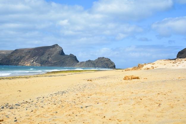 Vista deslumbrante da praia de porto santo com uma enorme formação rochosa