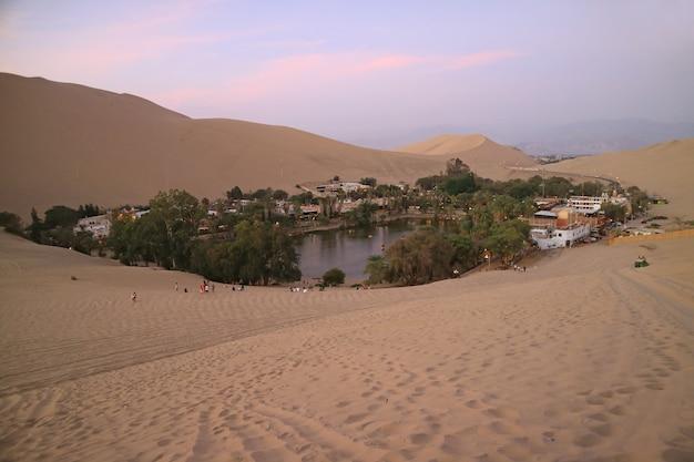 Vista deslumbrante, de, huacachina, a, oasis, cidade, como, visto, de, a, duna areia, em, pôr do sol, ica, peru