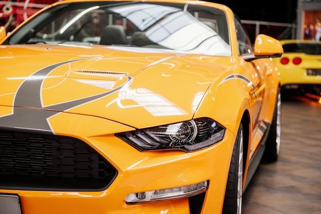 Vista deslumbrante de perto da frente de um automóvel amarelo de luxo dentro de casa