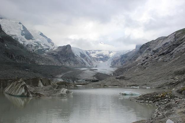 Vista deslumbrante de um lago cercado por belas montanhas cobertas de neve em um dia de neblina