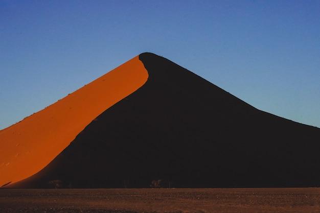 Vista deslumbrante de uma bela duna de areia sob o céu azul na namíbia, áfrica