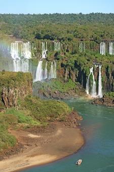 Vista deslumbrante do lado brasileiro das cataratas do iguaçu com arco-íris e barco no rio iguaçu, brasil