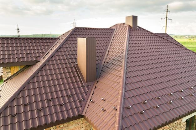 Vista detalhada do telhado da casa coberto com telhas de metal marrom.