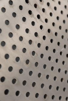 Vista diagonal da superfície de metal afiada perfurada.