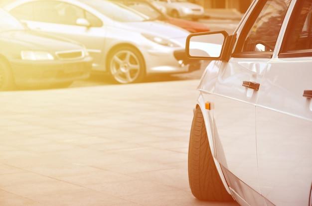 Vista diagonal de um carro branco brilhante que fica em um quadrado de azulejos cinza