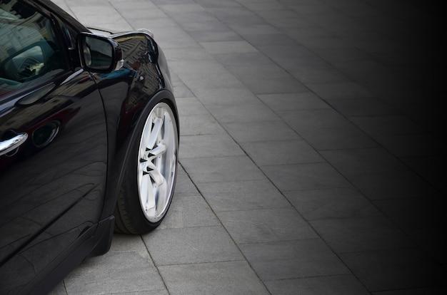 Vista diagonal de um carro preto brilhante com rodas brancas, que fica em um quadrado de azulejos cinza