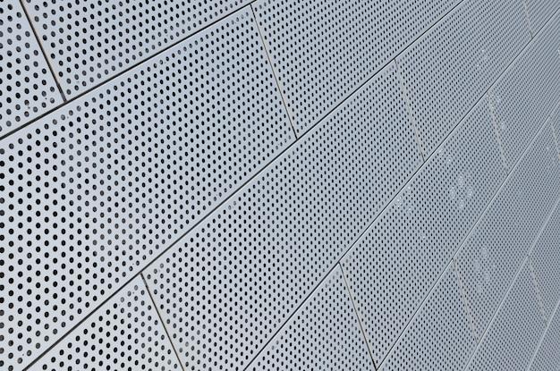 Vista diagonal dos painéis de padrão de pontos de metal na superfície do teto