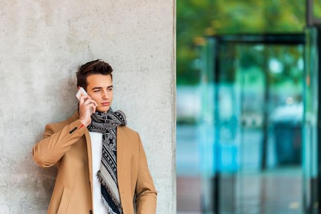 Vista dianteira, de, elegante, homem jovem, desgastar, roupa denim, inclinar-se, ligado, um, parede, enquanto, usando, um, telefone móvel, ao ar livre