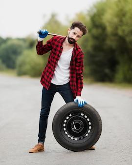 Vista dianteira, de, homem, com, chave, e, pneu