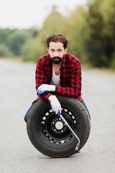Vista dianteira, de, homem, com, pneu, e, chave