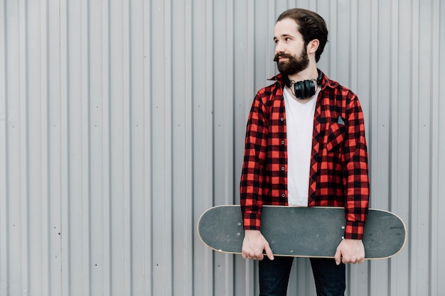 Vista dianteira, de, homem, segurando, skateboard