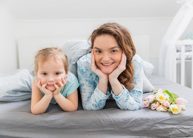 Vista dianteira, de, mãe filha, olhando câmera, enquanto, encontrar-se cama, casa