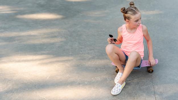 Vista dianteira, de, menina, sentando, ligado, skateboard