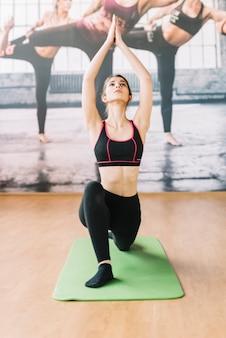 Vista dianteira, de, mulher, fazendo, ioga, em, ginásio
