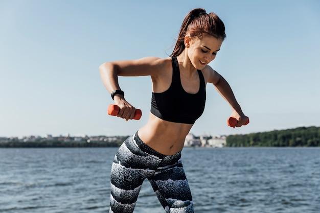 Vista dianteira, de, mulher, fazendo, treinamento peso