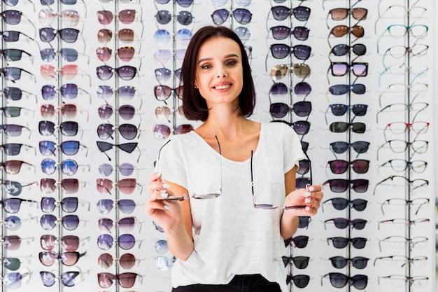 Vista dianteira, de, mulher segura, óculos de sol, pares