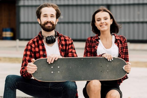 Vista dianteira, de, par, segurando, skateboard