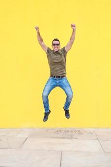 Vista dianteira, de, um, homem jovem, óculos sol saltando, contra, um, amarela, luminoso, parede, em, um, ensolarado, dia