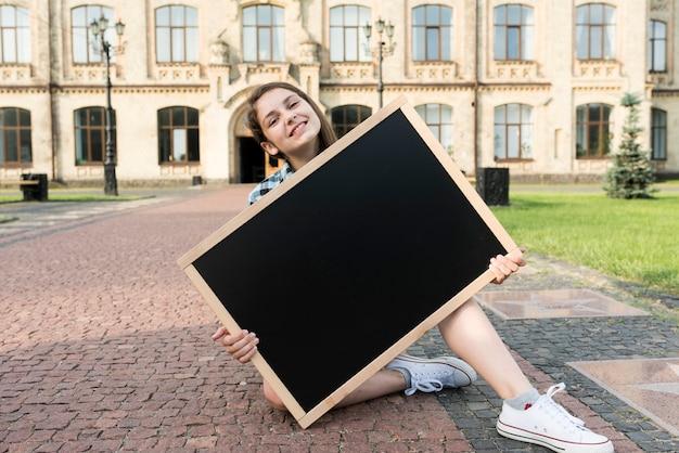 Vista dianteira, menina adolescente, segurando, quadro-negro
