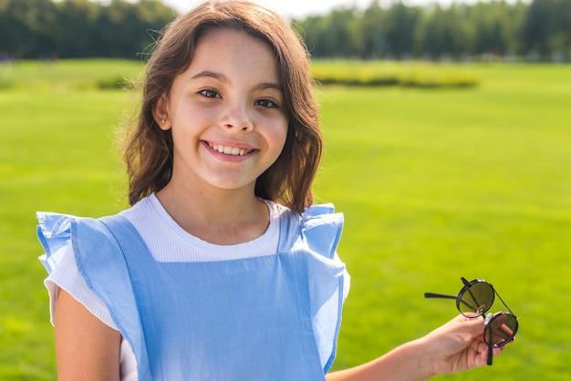 Vista dianteira, menininha, segurando, fresco, óculos de sol