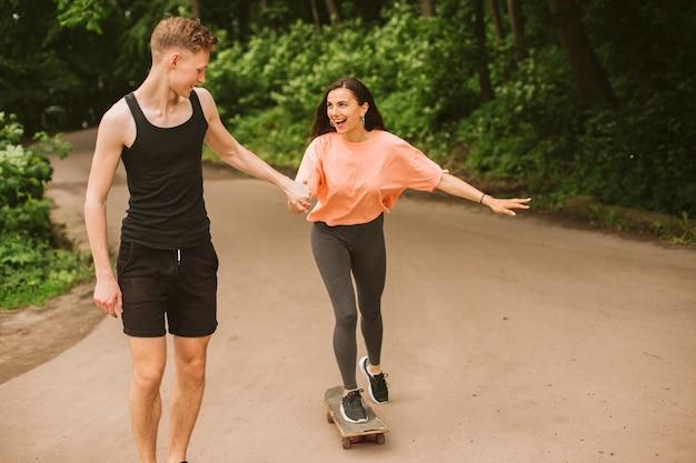 Vista dianteira, menino, ajudando, menina, skateboarding