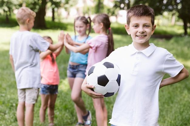 Vista dianteira, menino, segurando, um, bola futebol