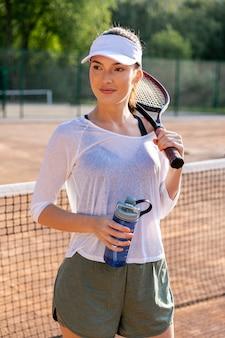 Vista dianteira, mulher, hidratar, ligado, quadra tênis