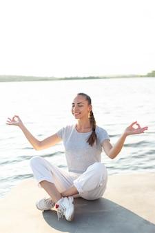 Vista dianteira, mulher meditando, ligado, doca