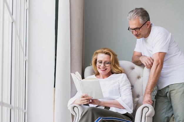 Vista dianteira, par velho, lendo um livro
