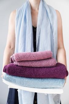 Vista dianteira, pessoa, segurando, empilhado, toalhas