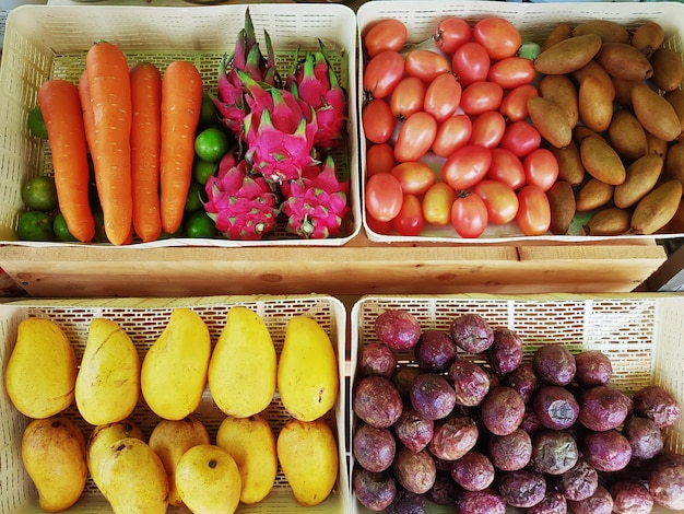 Vista diretamente acima das bandejas de vários tipos de frutas e vegetais tropicais para fazer batido